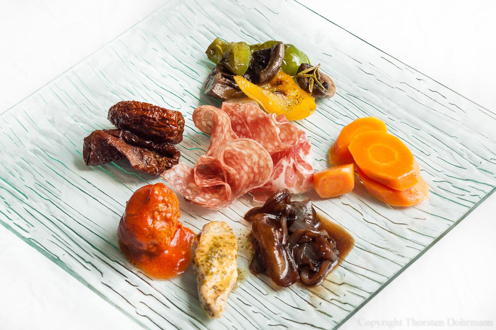 Gemischte Antipasti - im Uhrzeigersinn von oben: Gebratenes Gemüse in Olivenöl, glasierte Karotten mit Knoblauch, Balsamico-Zwiebeln, Schweinerücken in Limettensauce, Hackbällchen in Tomatensauce, getrocknete Tomaten